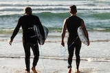 two me holding surfboards at the water's edge