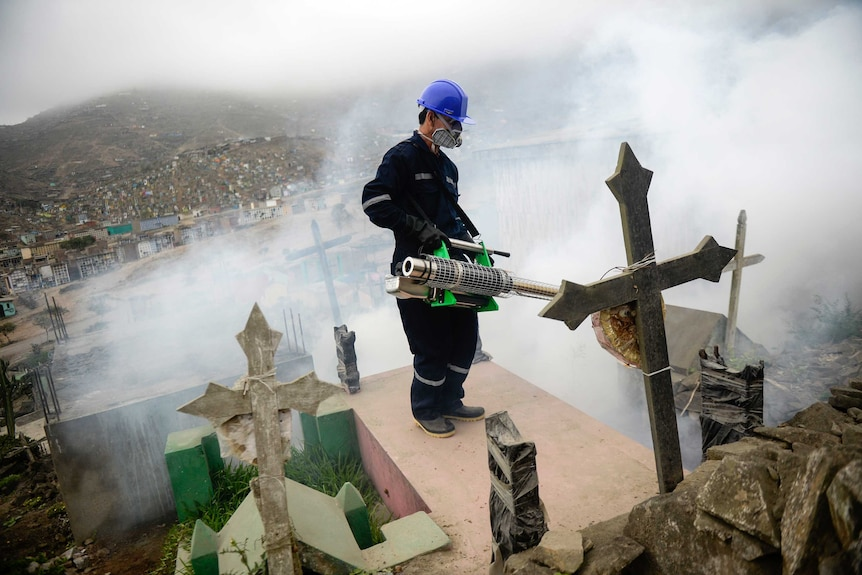 A man wearing protective clothing against Zika virus sprays grave stones with a fumigation machine