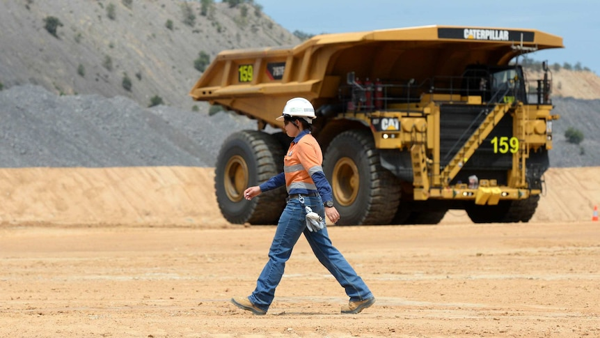 A female mine worker walks past a mine dump truck at a coal mine in central Queensland.