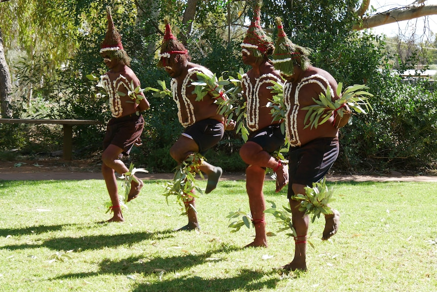 Four Indigenous men dance with their arms behind their backs, wearing leaves on their arms, legs, and heads.