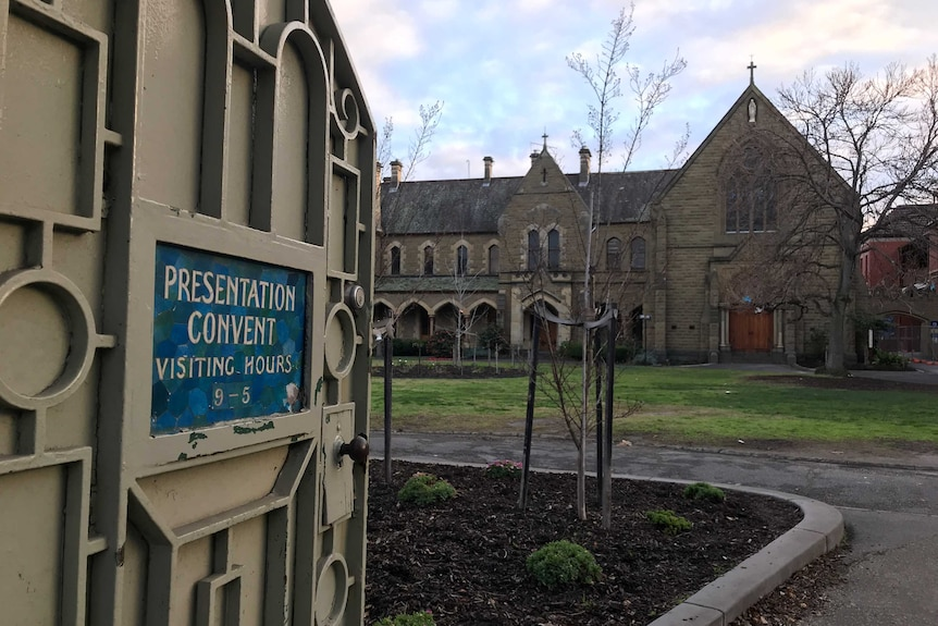 An open gate to the Presentation College buildings bears a sign reading 'Presentation Convent Visiting Hours 9-5'.