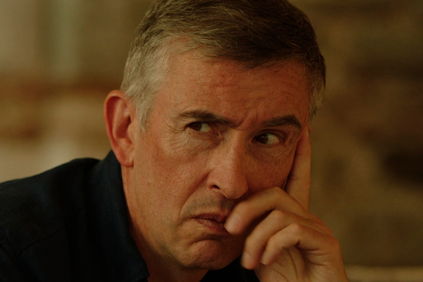 A man in black shirts with short greying dark hair makes serious expression and rests chin in hand, background is out of focus.