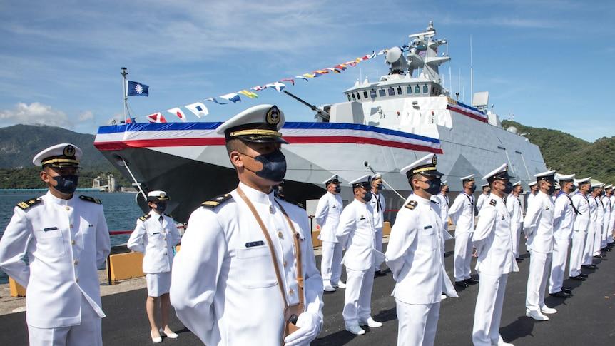 台湾海军陆战队员身着白色制服站在一艘新船前