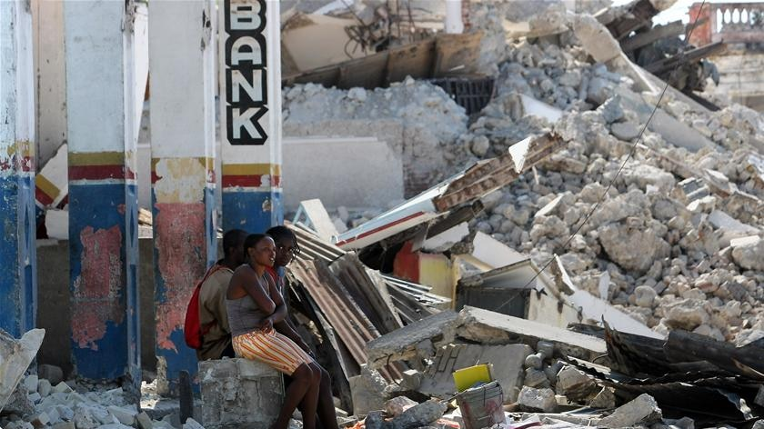 Haitians sit in the rubble of a destroyed church