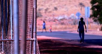 A youth walks down a street in Roebourne alongside a metal fence.