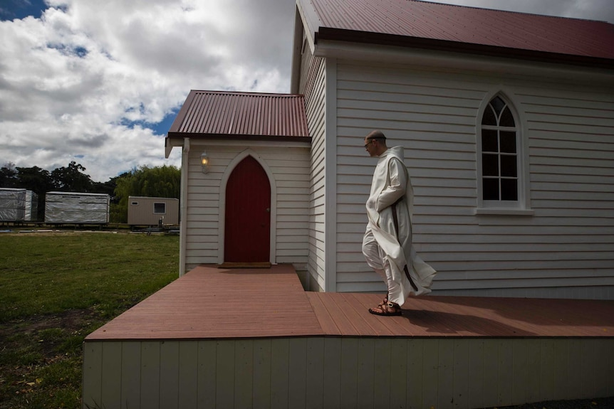 A Benedictine monk walks outside a small church.