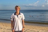 Blonde-haired boy in white t-shirt standing on beach smiling.