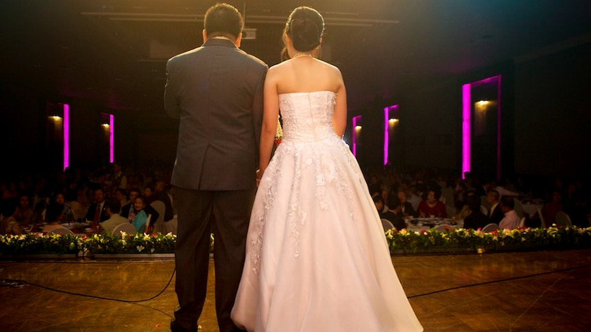 Married couple stand on stage in front of the crowd at their reception.