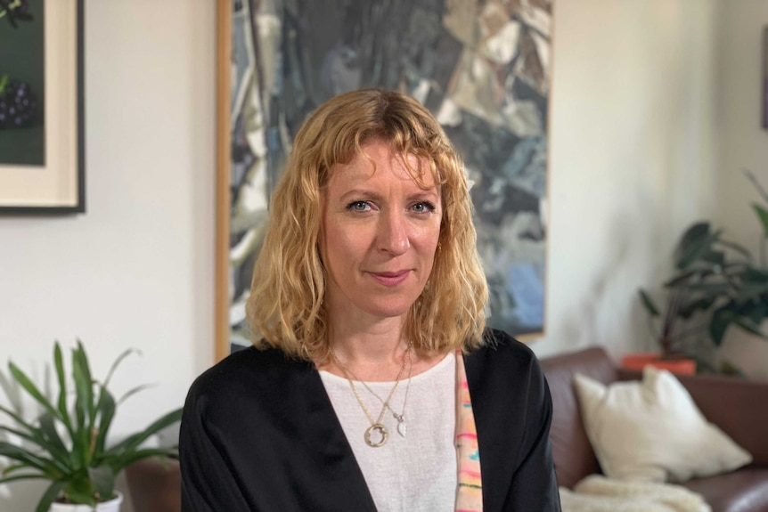 Jemma Burns sits in a living rooms smiling at the camera.