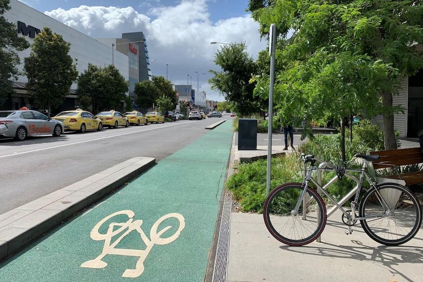 A bike locked in a bike rack beside a green bike lane on a city street.