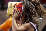 A young fan makes sure her popcorn is finished during a sporting event