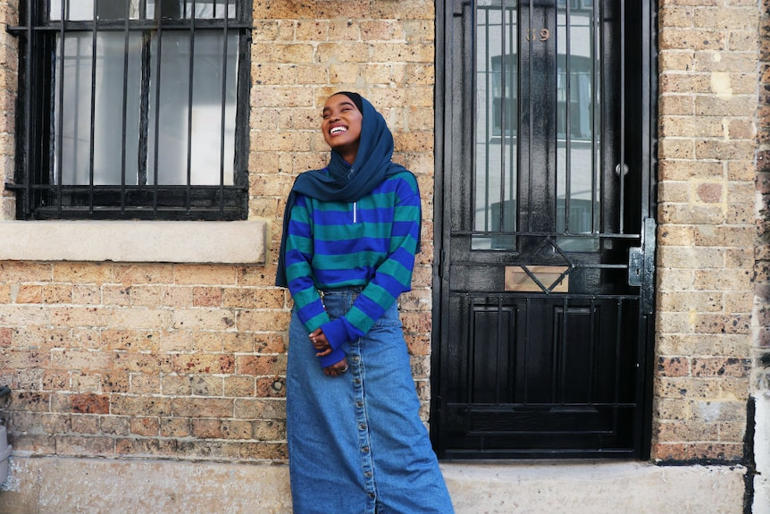 Hijabi model Miski Omar poses in a long denim skirt in front of brick house to depict modest fashion trend.