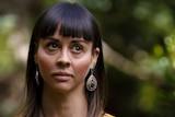 A woman looks sad amongst trees