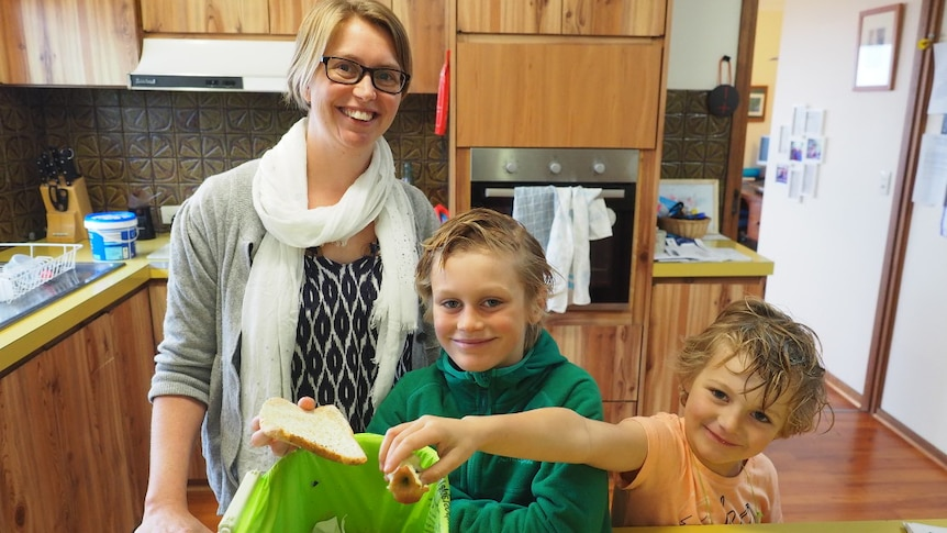 A mum and her two sons, aged 5 and 8, put fruit scraps in a small kitchen bin.
