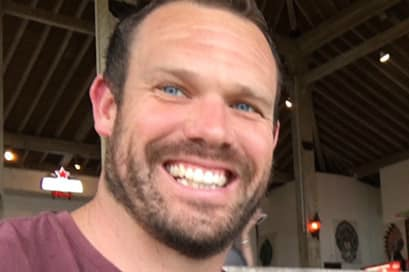 A man poses for a selfie and smiles in a bar