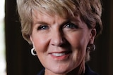 Julie Bishop looks into the camera while standing in a room with the curtains drawn.