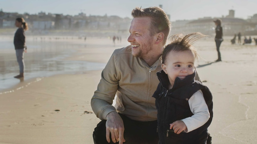 Sydney father Renn Holland and his child at the beach.