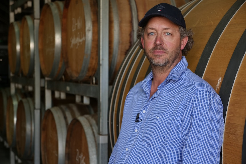 一个戴着鸭舌帽的男人站在酒窖旁。