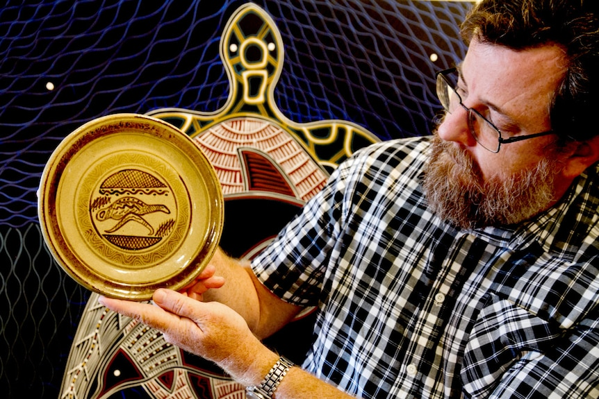 Exhibition co-curator Mathew Wengert hold up a dinner plate covered in Indigenous designs.