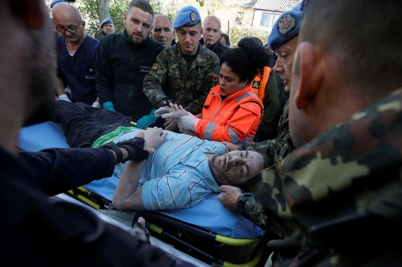 An injured man on a gurney as military is around him.