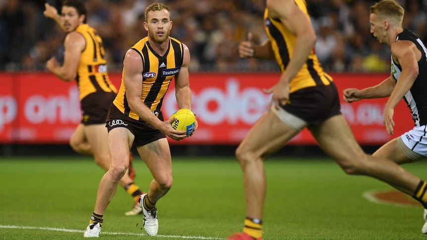 Hawthorn's Tom Mitchell (2nd L) handballs against Collingwood at the MCG on March 24, 2018.