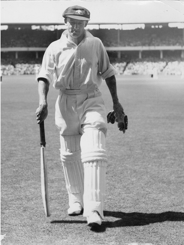 Don Bradman walking off with bat and gloves in his hands, baggy green on his head.
