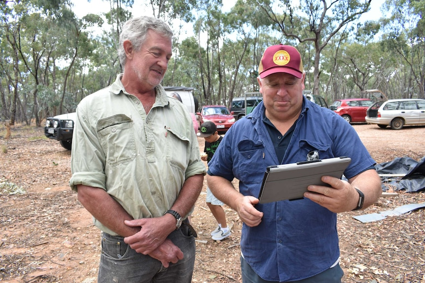 Two men look down at an ipad in bushland.
