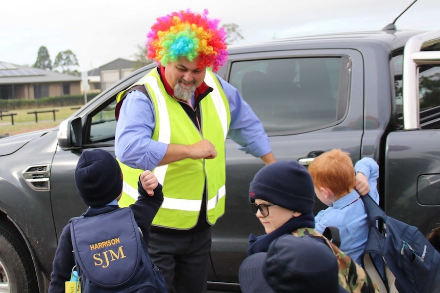 Male school principal wearing yellow hi-vis vest and multi-coloured curly clown wig dances with students