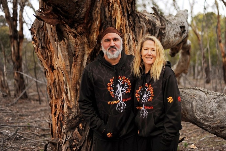 A man with a grey beard and a bandana stands with a blonde-haired woman in front of a huge tree