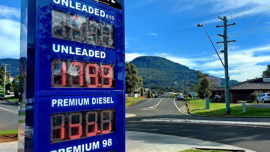 A petrol price board shows the unleaded price of 179.1c per litre, with an escarpment in the background.