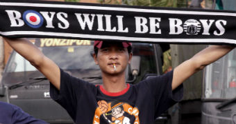 """A Persija fan holds a banner reading: """"Boys will be boys""""."""