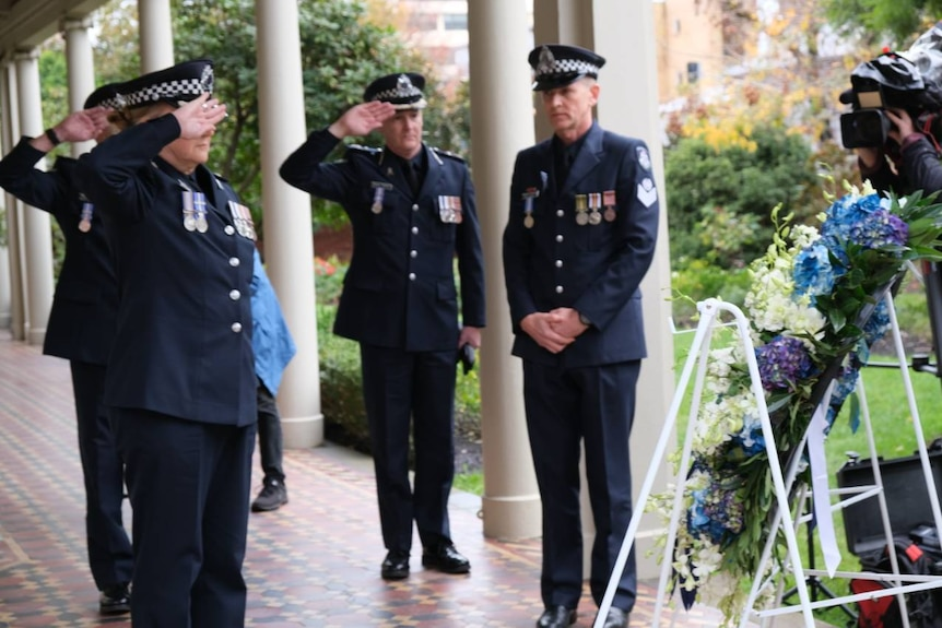 Victoria Police officers salute wreaths dedicated to two officers who were killed on the job.