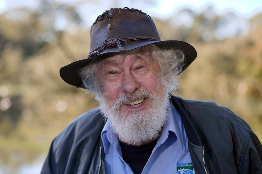 A smiling man is an old battered hat and a bushy grey beard.