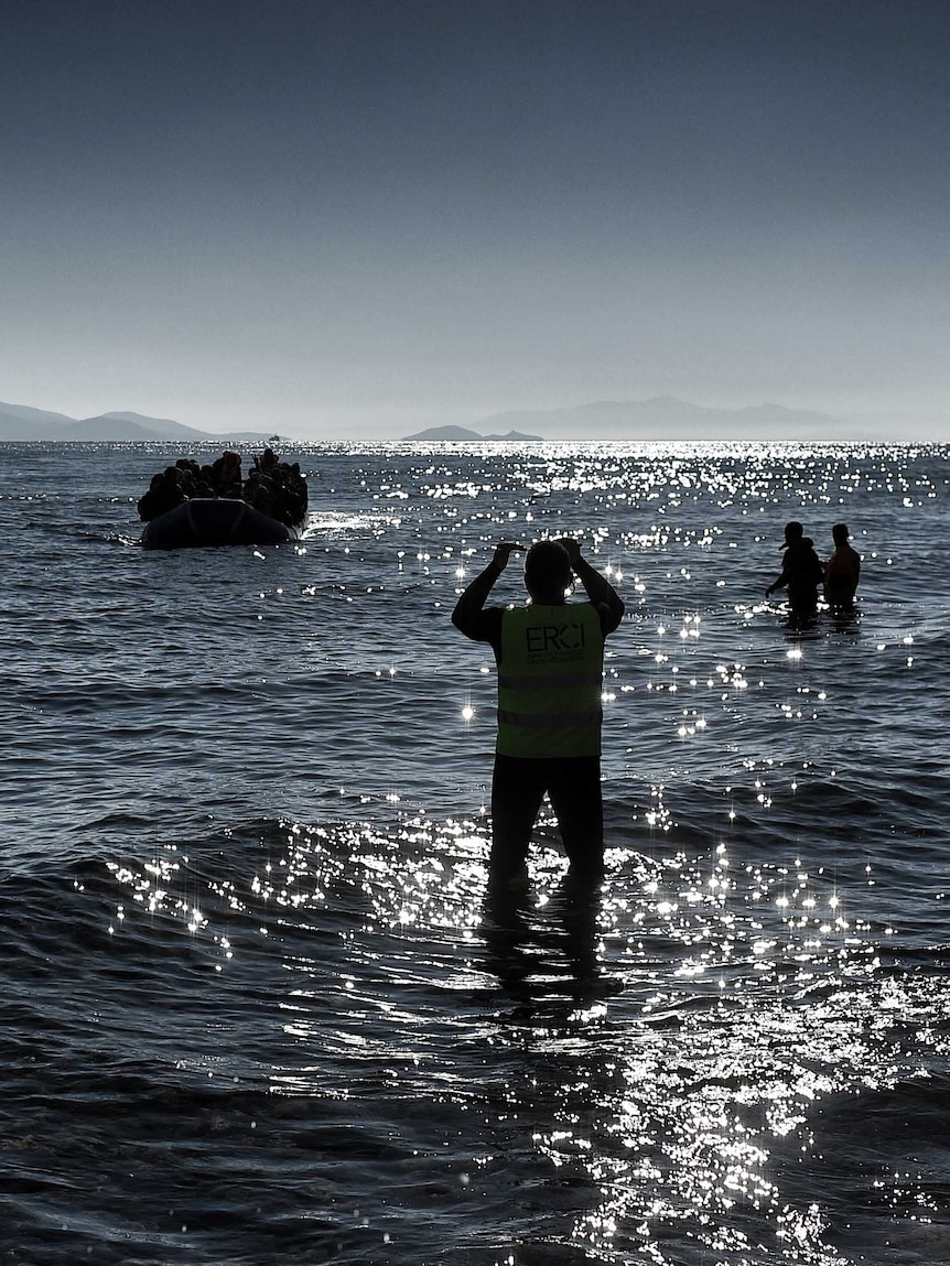 Members of the non-profit organisation Emergency Response Centre International (ERCI) gesture from the shore to a boat carrying refugees and migrants as it arrives in Greece