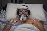 A man in bed with his eyes closed, with an oxygen mask on.