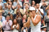 A young woman in tennis whites reacts emotionally on a grass court in front of cheering fans.