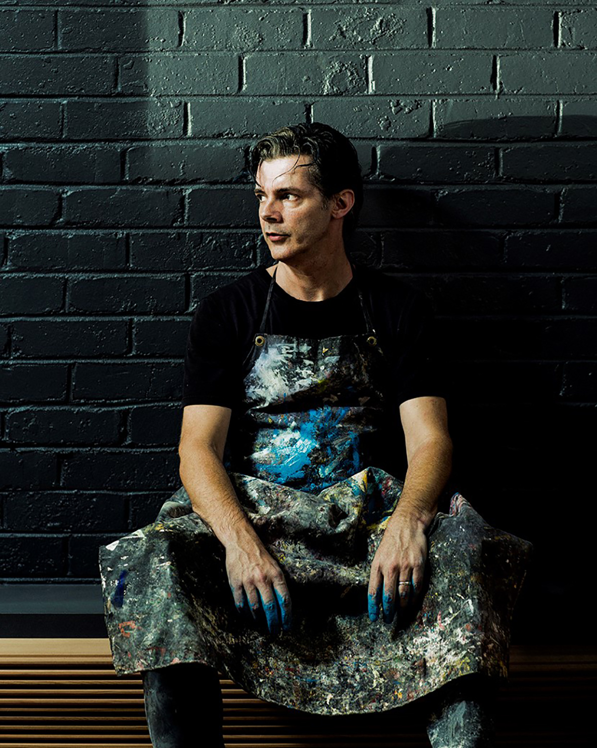 Colour photograph of Paint-maker and author David Coles wearing a paint smattered apron and sitting against a black wall.