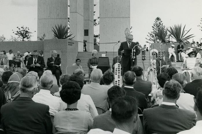 Black and white photo of official opening ceremony of Point Danger lighthouse with dignitaries seated as Mayor speaks