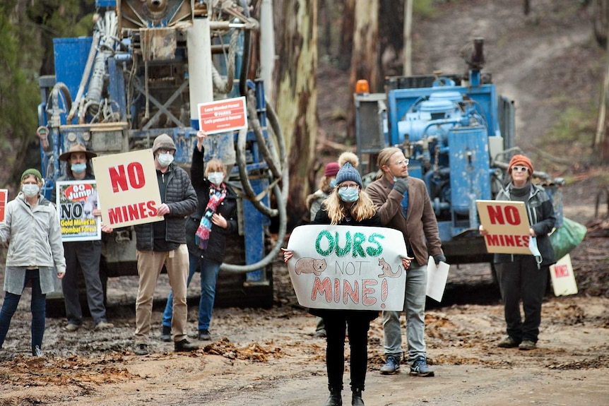 Protesters stand with signs in front of drilling equipment in a central Victorian forest