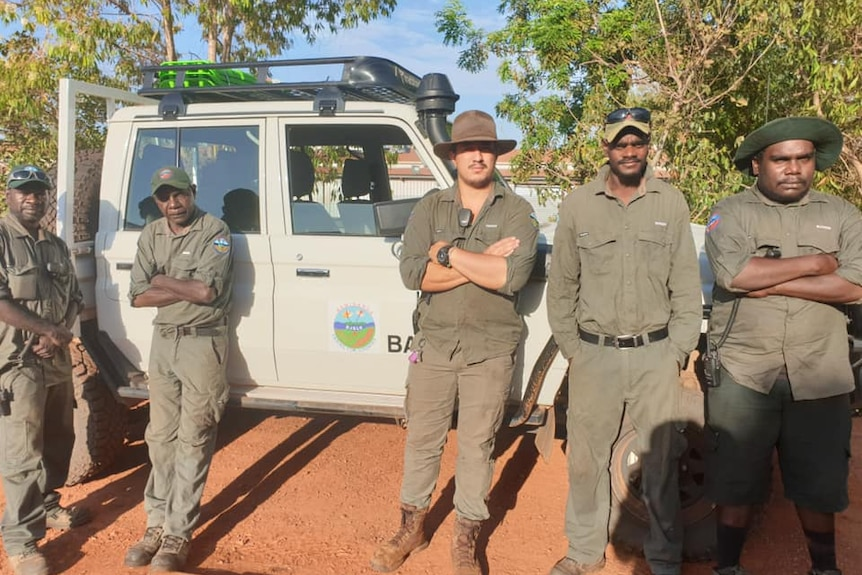 Five Bawinanga rangers in green uniform stand in front of a white ranger vehicle.