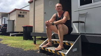 Man sitting on step outside a donga