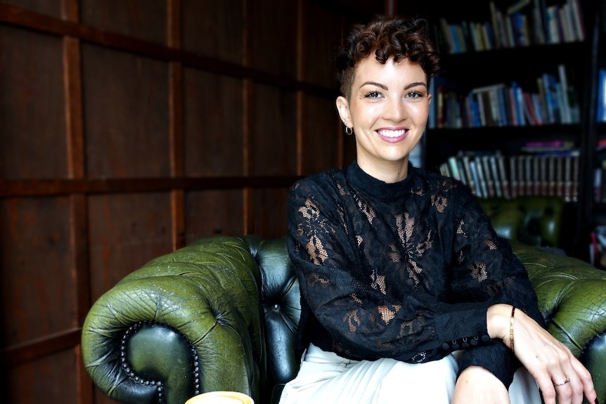 A young woman with curly short hair smiles while siting on a green chesterfield sofa chair.
