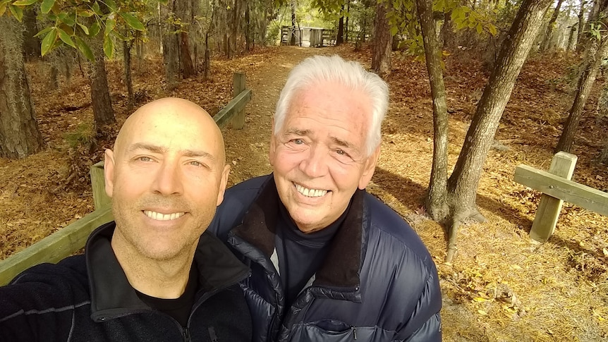Father and son taking a selfie in a forest.