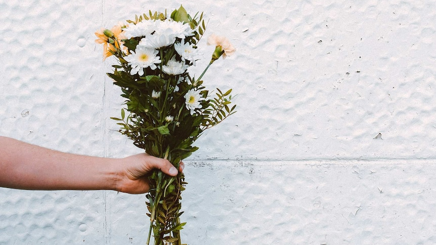Person holding a bunch of white and peach-coloured flowers for a story about apologising for past bullying and bad behaviour.