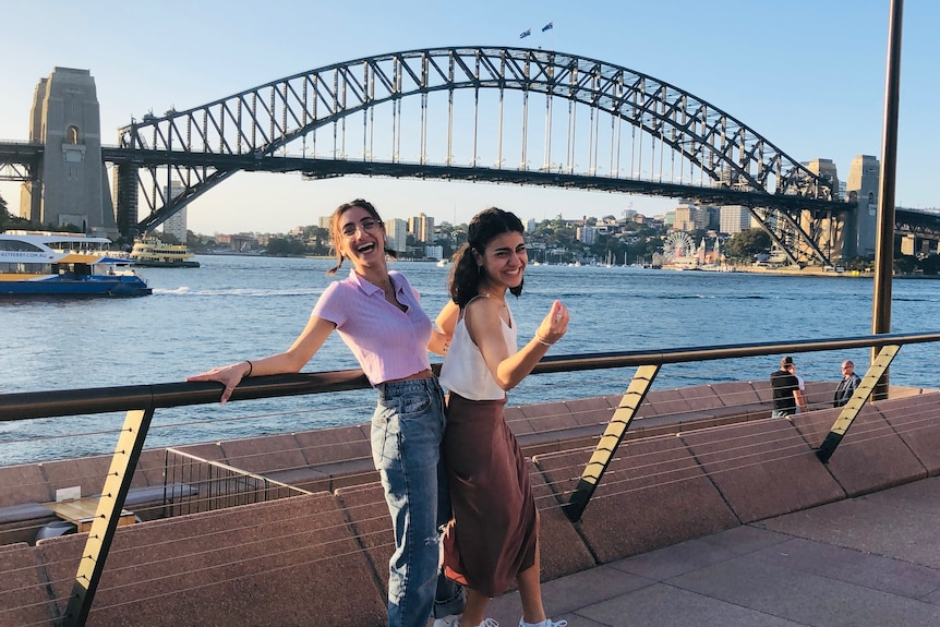 Two women smile for the camera as they stand by a railing in front of the Sydney Harbor Bridge.