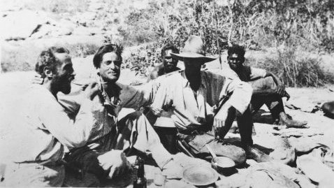 A black and white picture of Adolph Klausmann, Hans Bertram, Gordon Marshall and two Aboriginal men sitting on the ground.