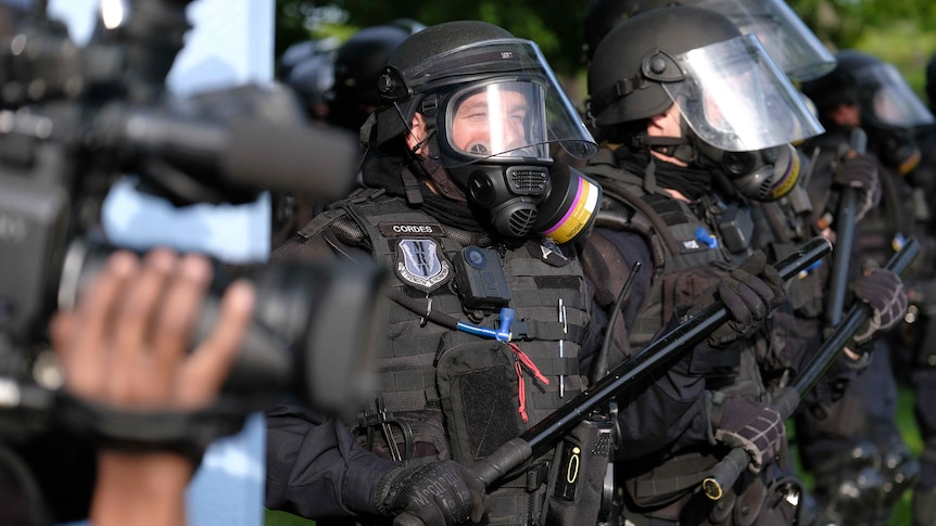 Man wearing police riot gear including black helmet, mask and shield