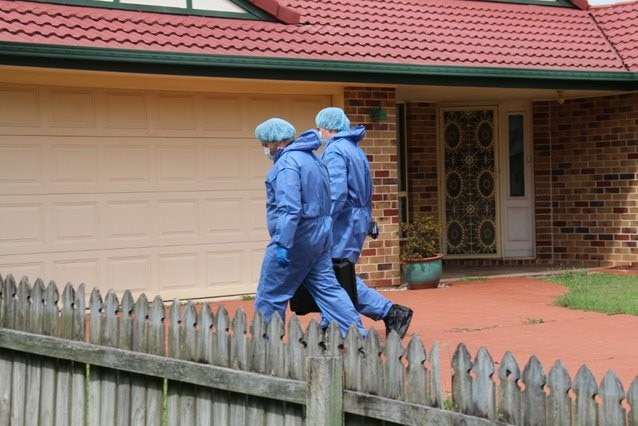 Two people in blue suits enter a home.