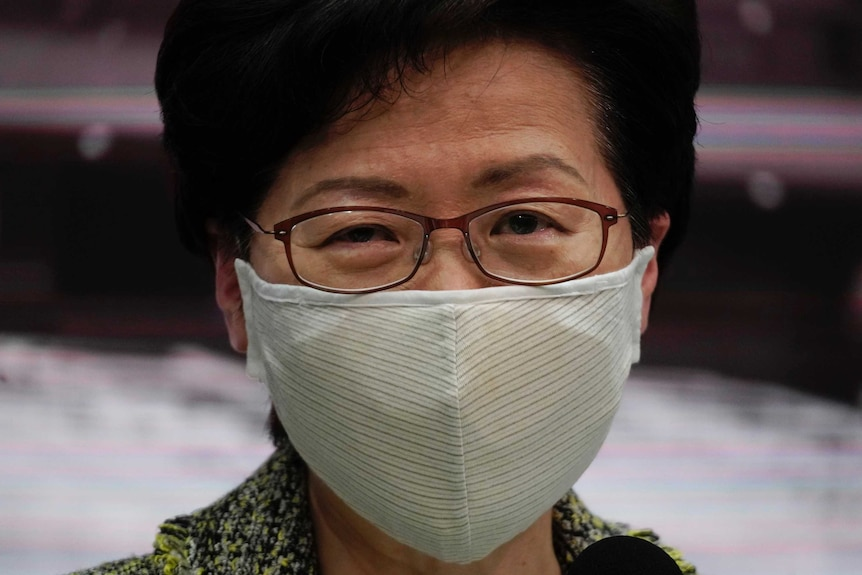 Hong Kong Chief Executive Carrie Lam wears a mask and looks at the camera.