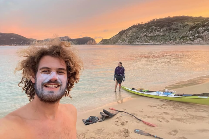two men with kayaks on a beautiful island